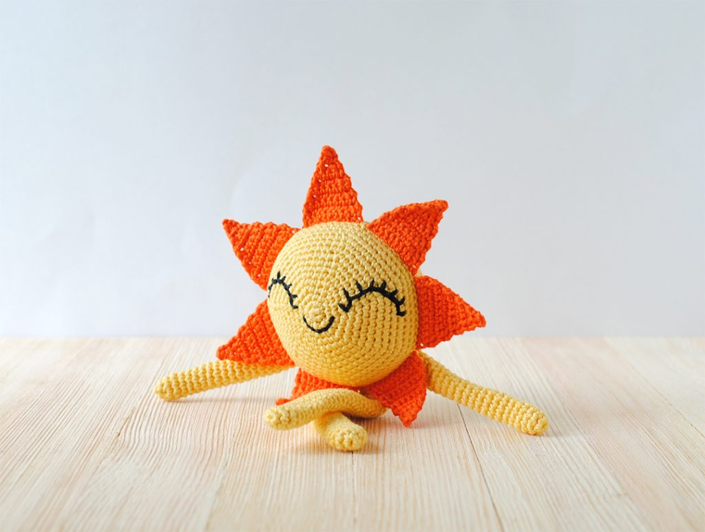 Picture of the aamigurumi Sun doll with arms and legs sitting down. Made with the free amigurumi crochet pattern by Tiny Curl.