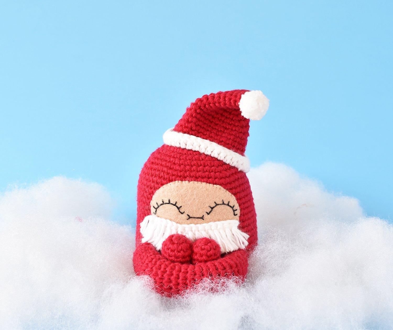 Curlie amigurumi doll sitting cozy in a cloud wearing her crochet Santa Hat and Beard.