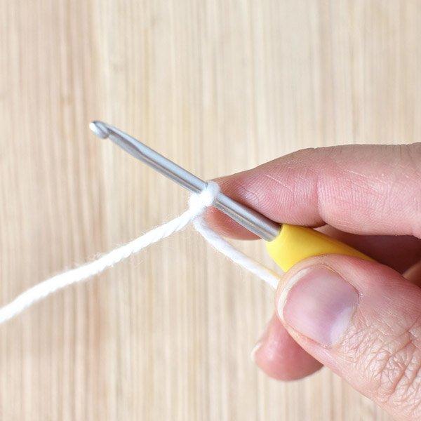 crochet hook doing a standing double crochet stitch using white yarn.