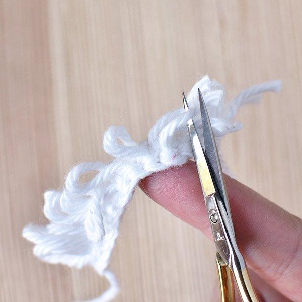 Scissors cutting the white yarn loop stitches for the crochet Santa beard.