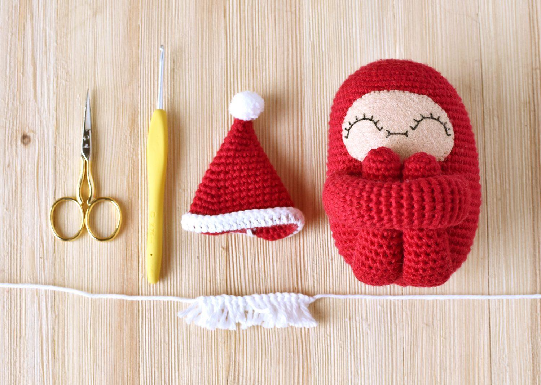 From left to right; crochet scissors, crochet hook, crochet Santa Hat, amigurumi curlie doll. Beneath them; crochet Santa Beard.