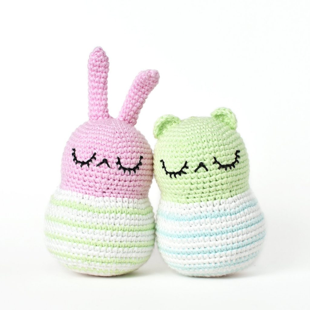 An amigurumi spring bunny and amigurumi bear leaning up against one another. The spring bunny is pink and the amigurumi bear is light green.