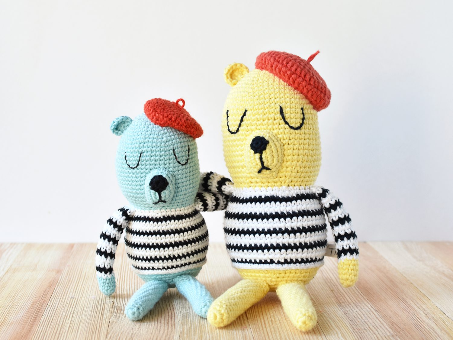 One small blue French bear and one large yellow French bear sit side by side on a wooden plank.