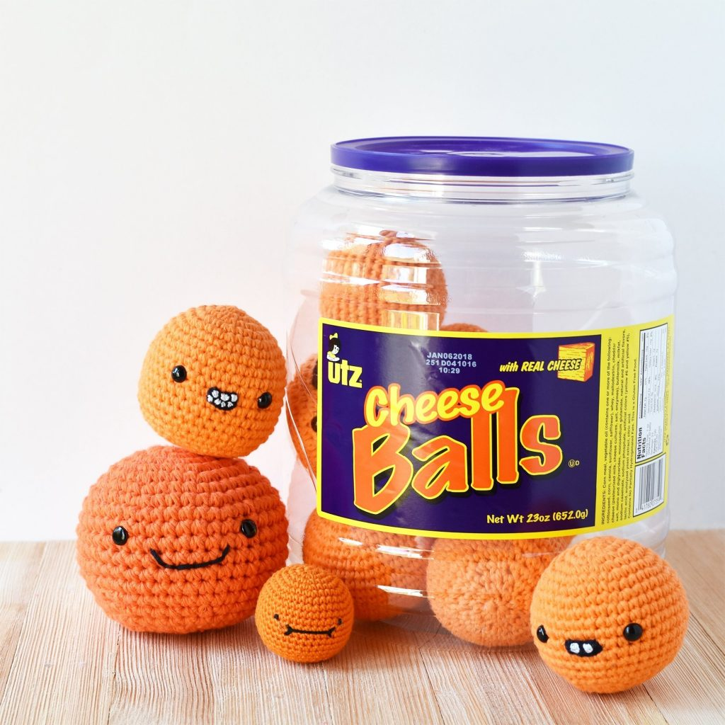 A cheese ball tub filled with crocheted cheese puffs with some stacked on each other. Crocheted cheese puffs made with this free crochet pattern
