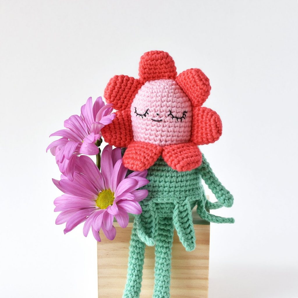 Picture shows Flower Gal Amigurumi doll sitting among wildflowers.