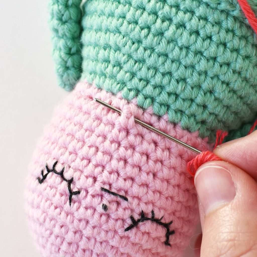Showing needle and yard placement for attaching a flower petal on the Flower Gal amigurumi doll's already embroidered face.