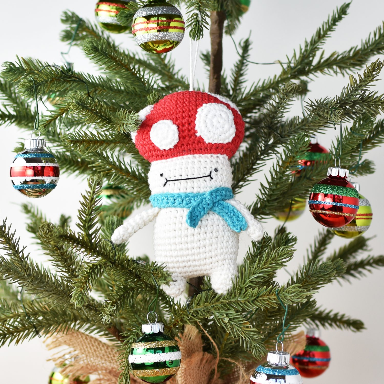 Free crochet Christmas ornament pattern, a free amigurumi crochet pattern by Tiny Curl. Crochet Christmas Ornament Mushie hanging on a Christmas tree.