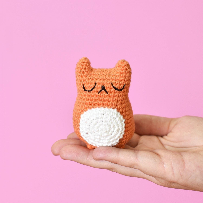 Free Amigurumi cat pattern. An amigurumi cat being held in a hand. Amigurumi cat is orange and white and was made with this free amigurumi cat pattern.