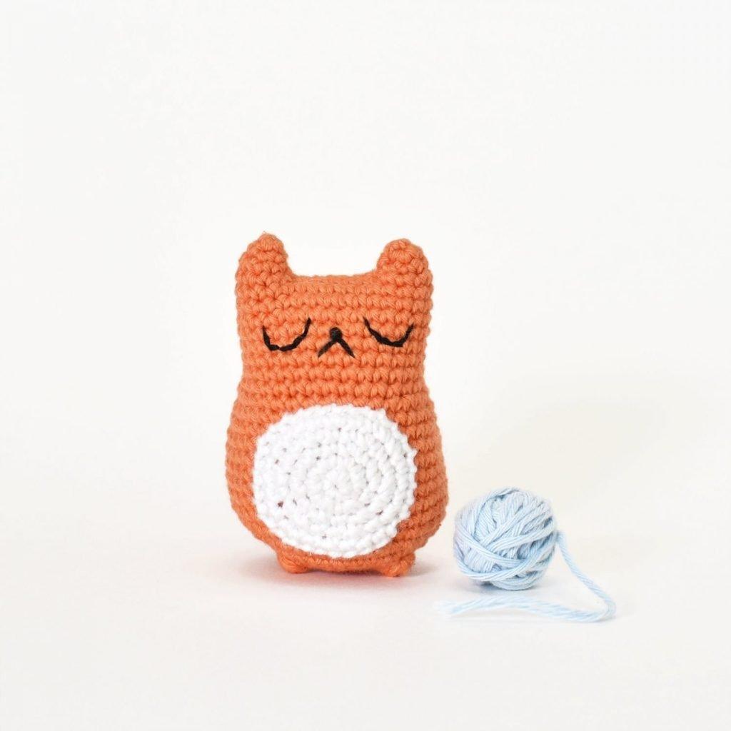 Free amigurumi cat pattern. An amigurumi cat sitting next to a tiny ball of yarn. Crocheted amigurumi cat was made with this free amigurumi cat pattern.