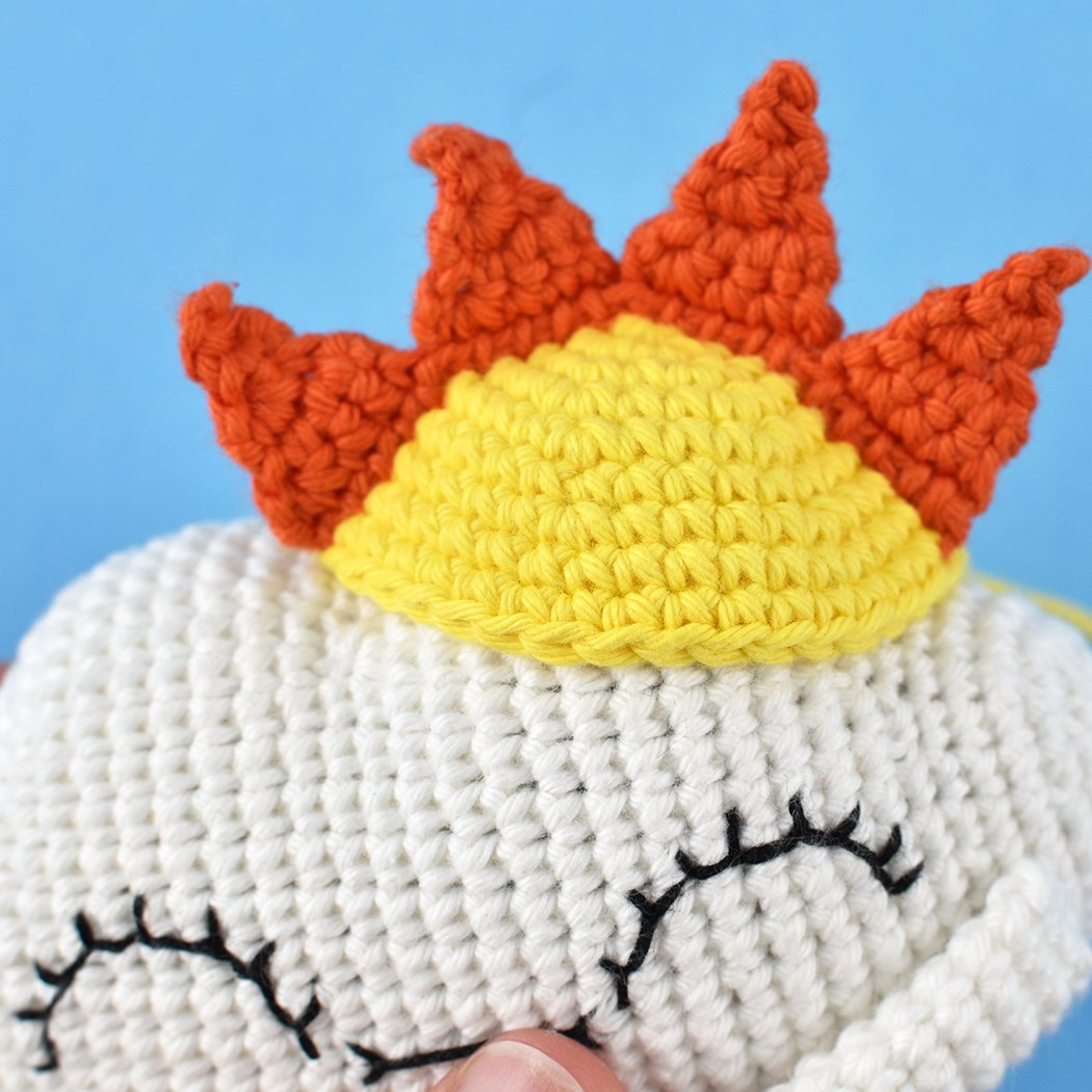 Close up of crocheted sun hat on top of crochet cloud doll.