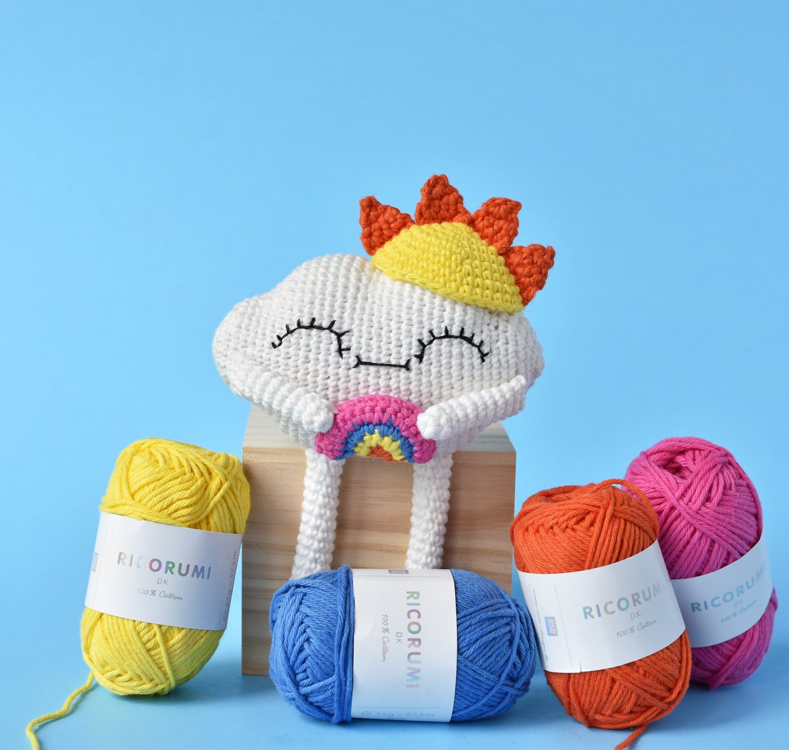 Amigurumi rainbow cloud crochet doll with a sun hat holding a rainbow sitting on a wooden box surrounded by balls of yarn for the rainbow.