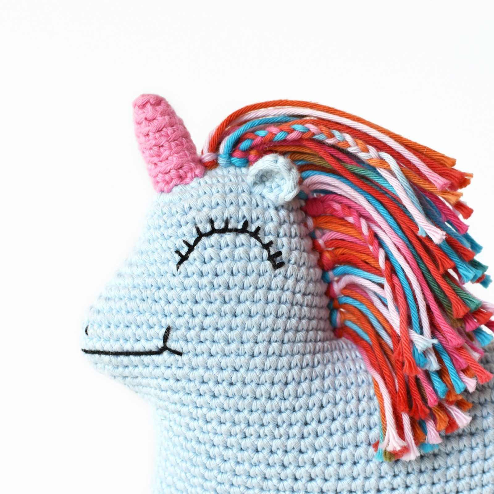 Up close face embroidery image for the amigurumi unicorn Uni Queen.
