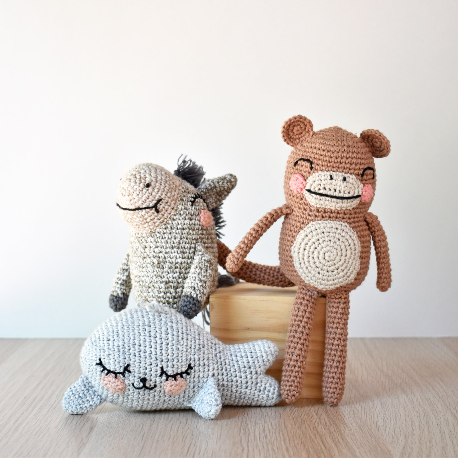 A crochet donkey, crochet monkey, and crochet seal stand on a wooden surface in front of a white backdrop.