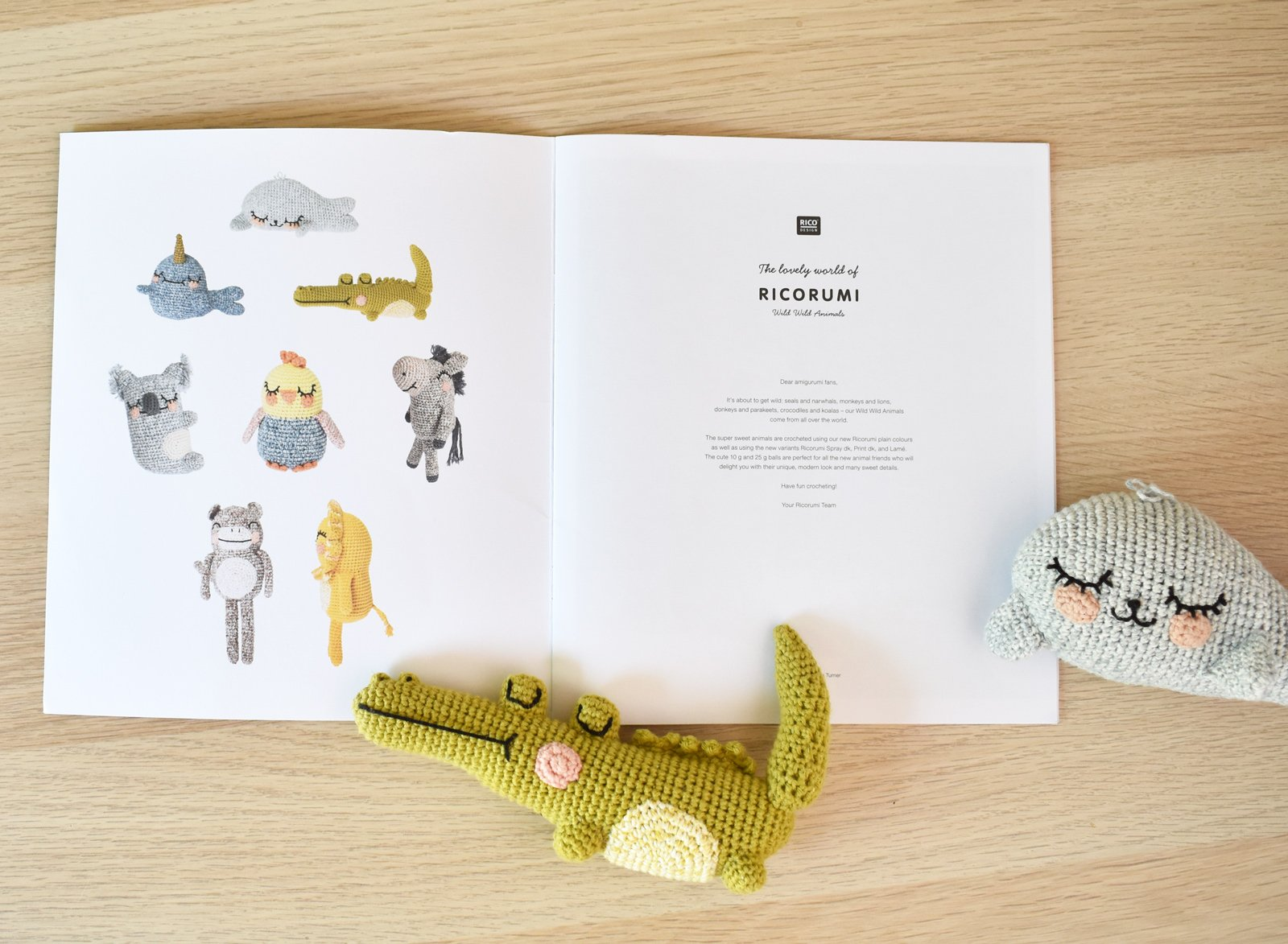 The Ricorumi Wild Wild Animals amigurumi pattern book sits opened on a wooden table. A crochet alligator and crochet seal sit on top of it.