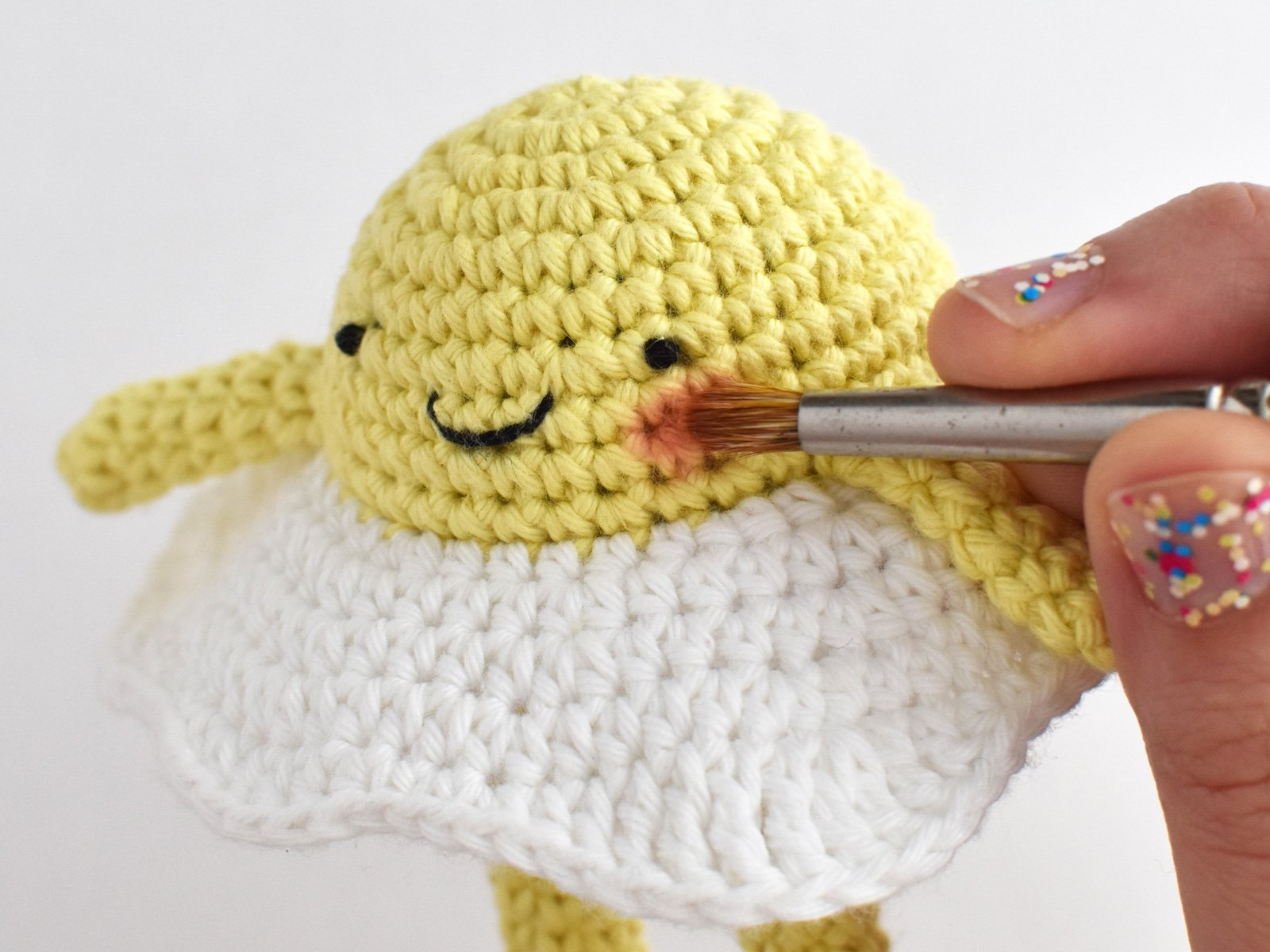 Close-up showing how to apply blush to the crochet egg amigurumi.