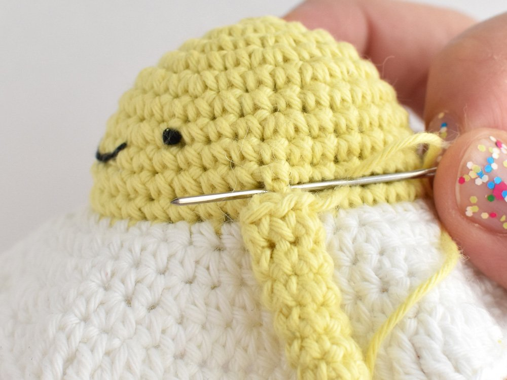 Close-up showing how to attaching the arm to the crochet egg amigurumi.
