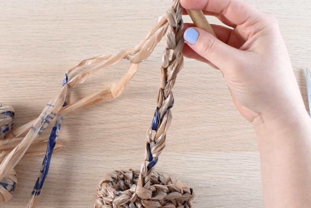 A chain rope made with 3 strands of plastic bag yarn extends from a crocheted plant pot cover.