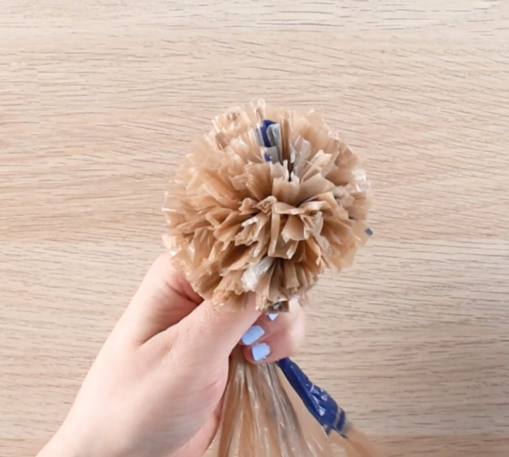 A hand holds a large pom pom made using plastic bag yarn.