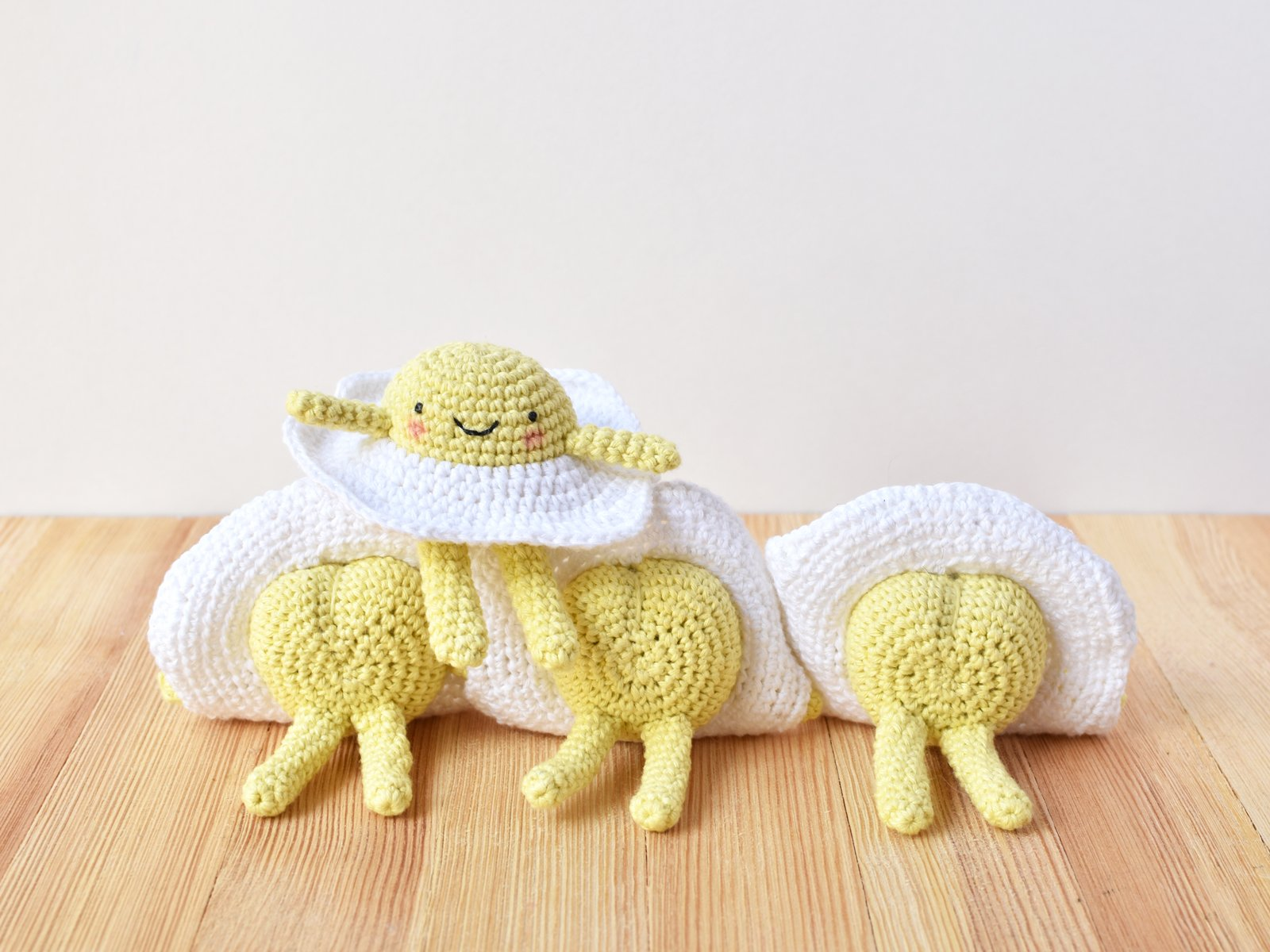 Crochet egg with arms and legs sitting on top of 3 other fried egg crochet dolls with their butts up.