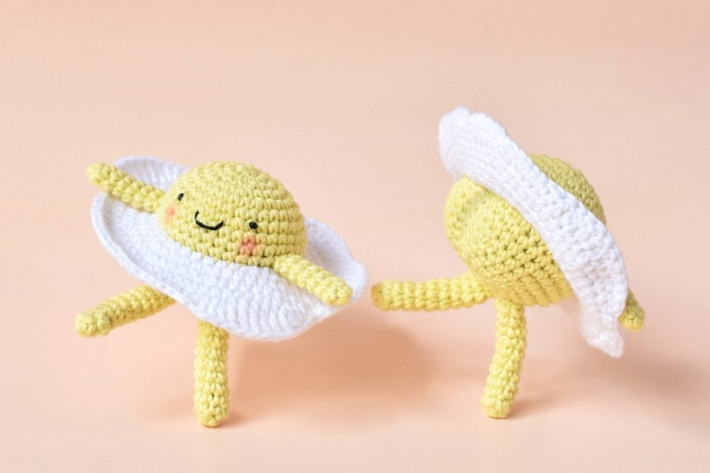 Two amigurumi crochet eggs on a pale pink background