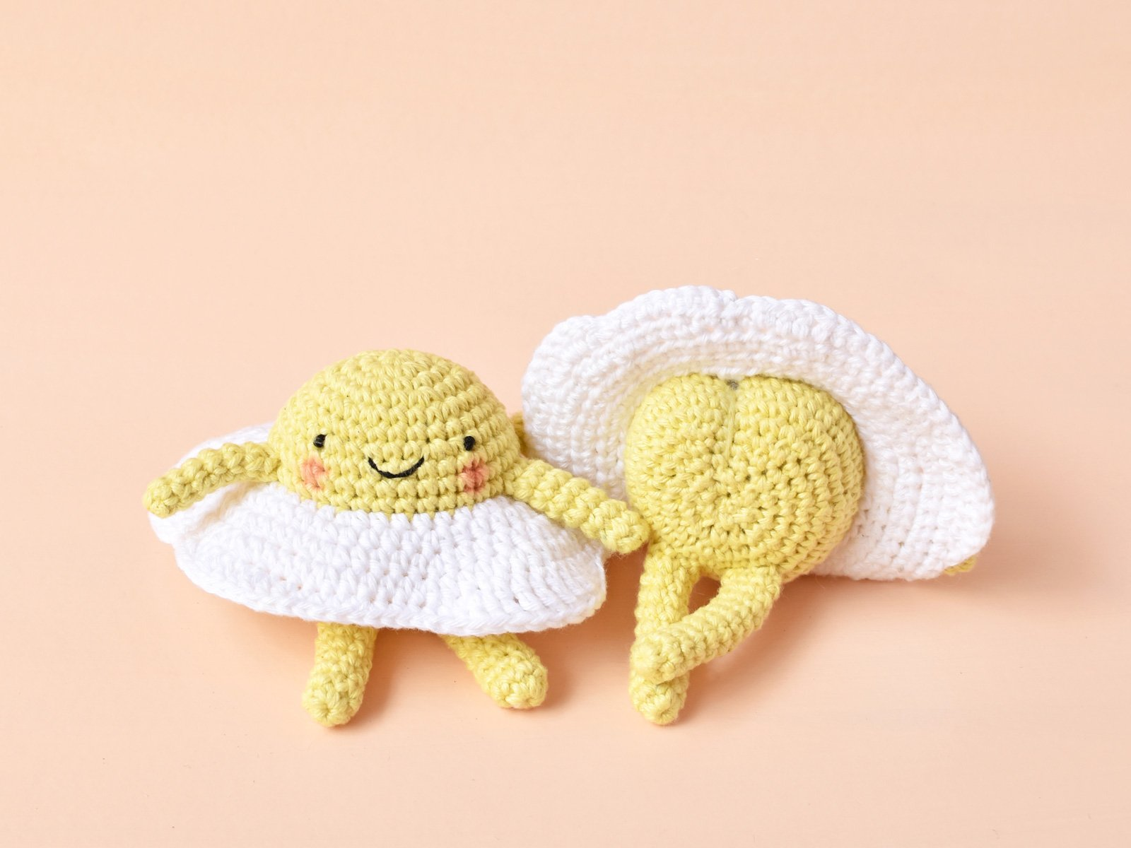 Two egg amigurumi sitting next to each other. One is facing the camera, the other is showing his butt. They are on a peach background.