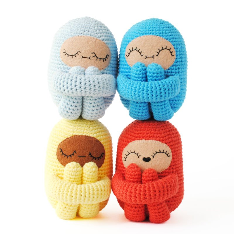 amigurumi dolls stacked up on a white background