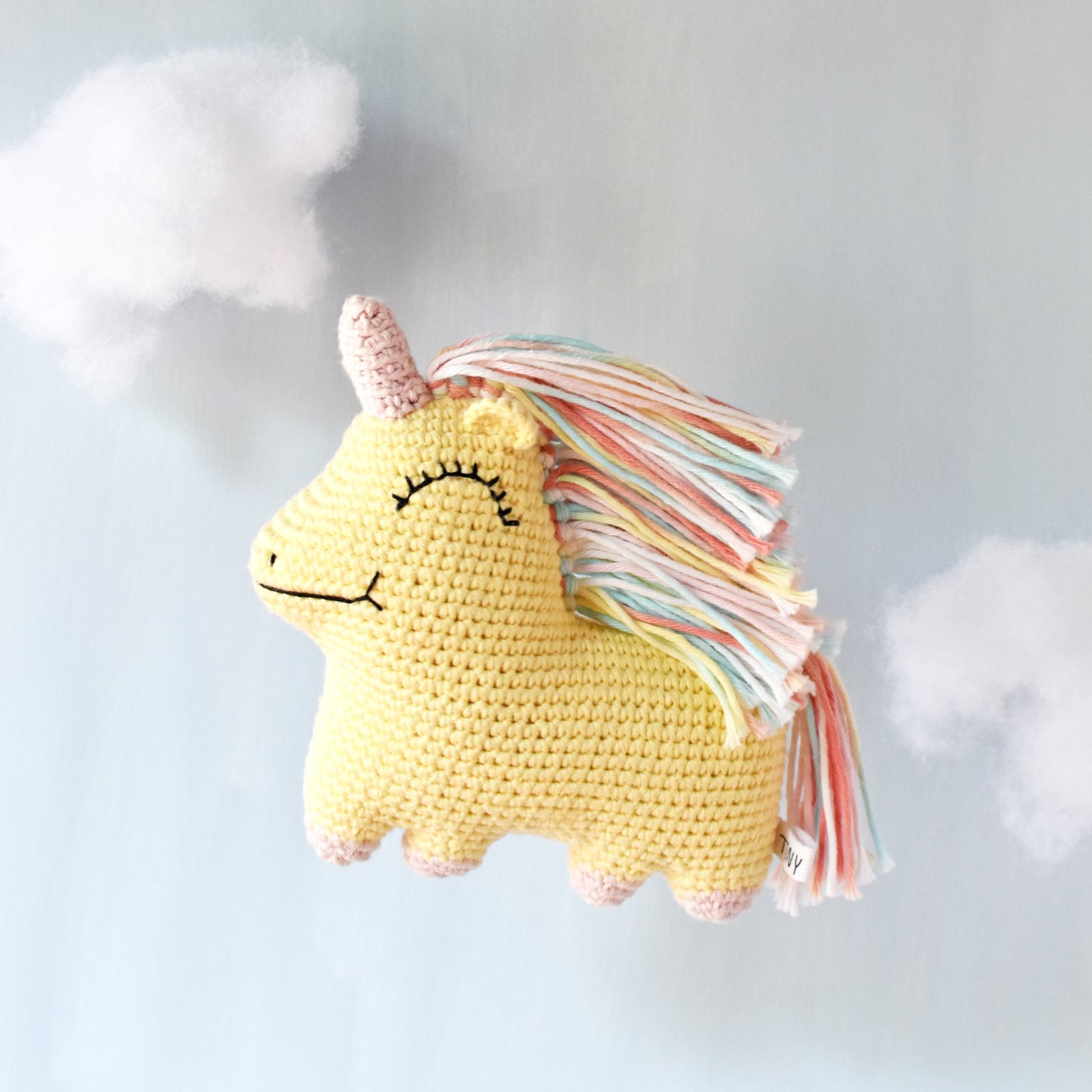 Yellow and pink pastel Uni Queen unicorn crochet doll flying in front of a pale blue background with clouds made of toy stuffing.