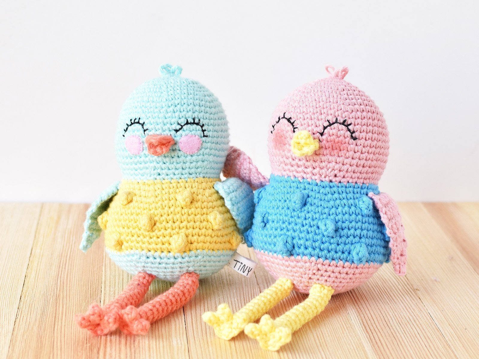 Two crocheted bird dolls sitting side by side on a wooden surface in front of a white background. The bird on the left is blue and yellow and the bird on the right is pink and blue.