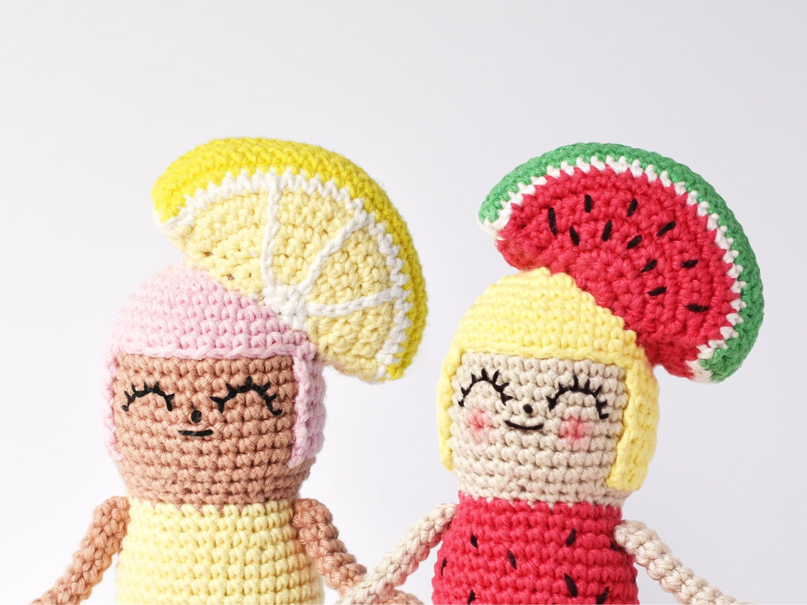 Close-up of crochet Lemon Girl doll and Watermelon Girl doll sitting side by side on a white background.