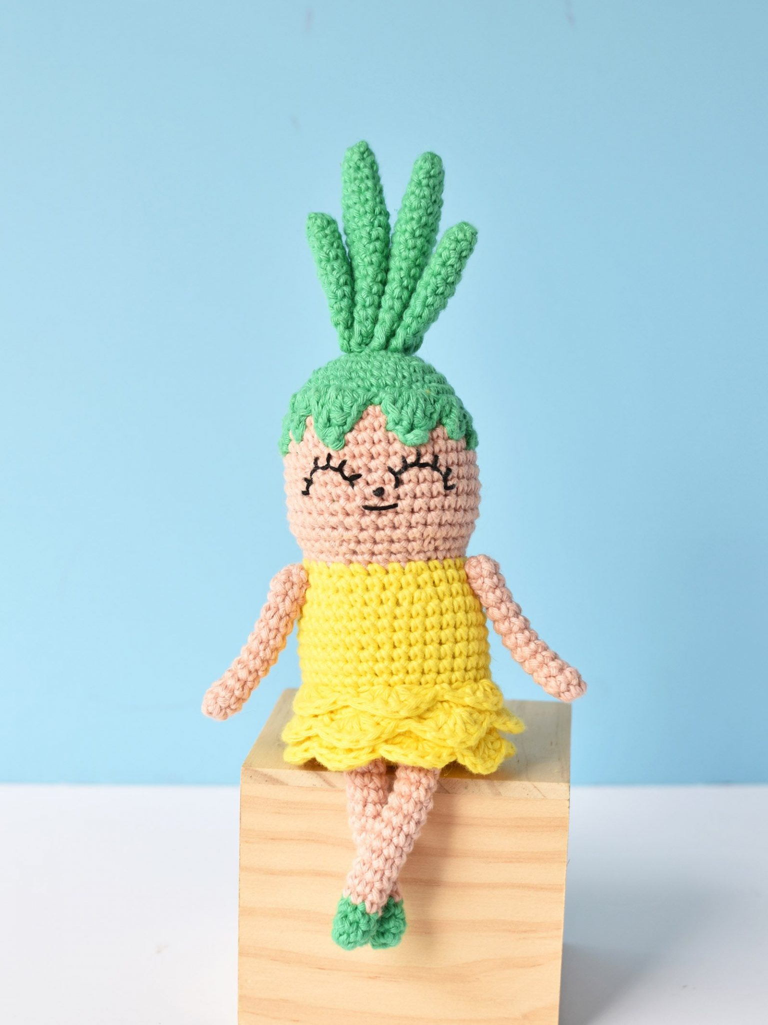 Crochet Pineapple amigurumi sitting on a wooden block in front of a blue background.