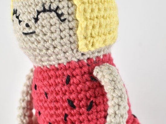 Close up of the side of crochet doll with arms fully attached.