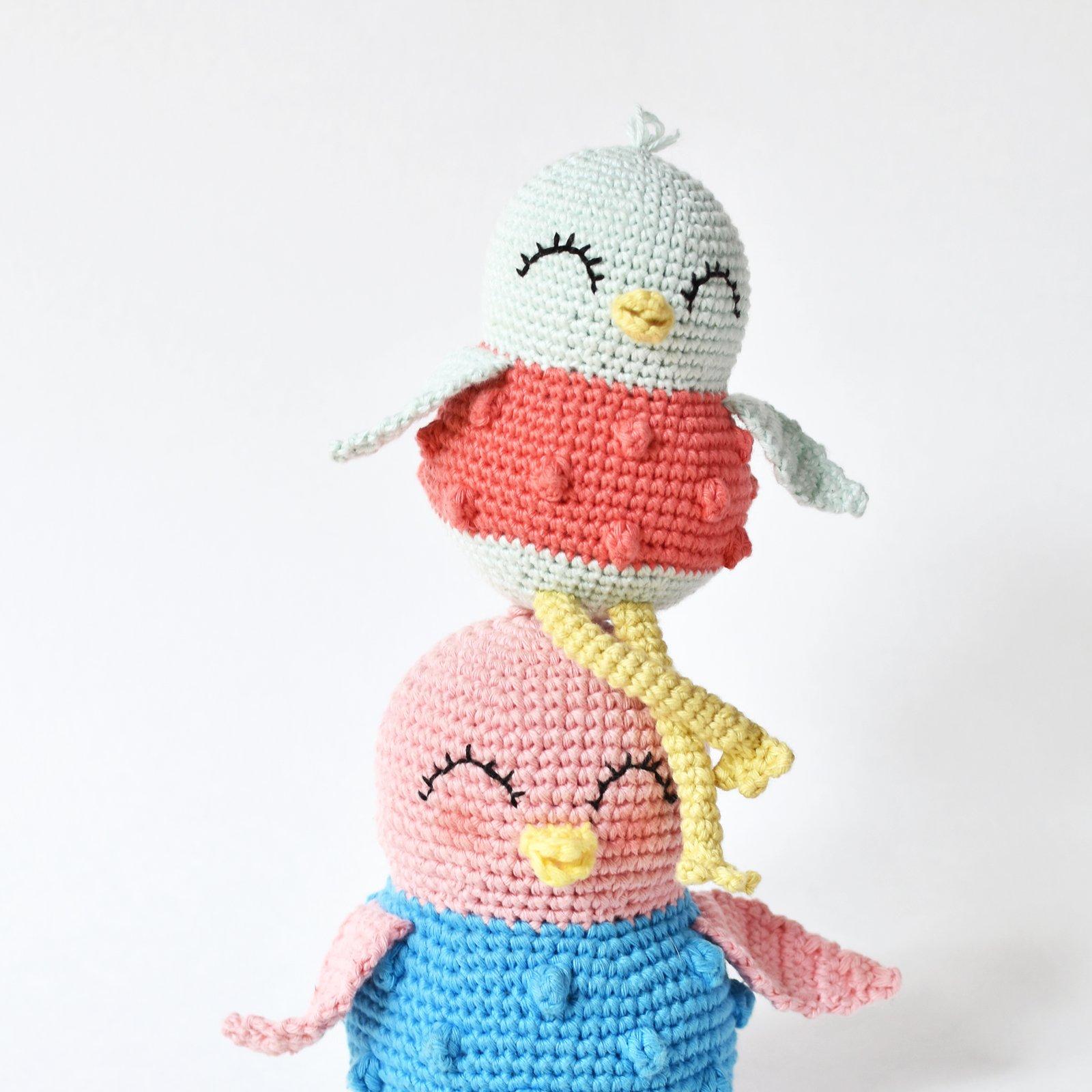 A smaller crochet bird sitting on top of another bird.