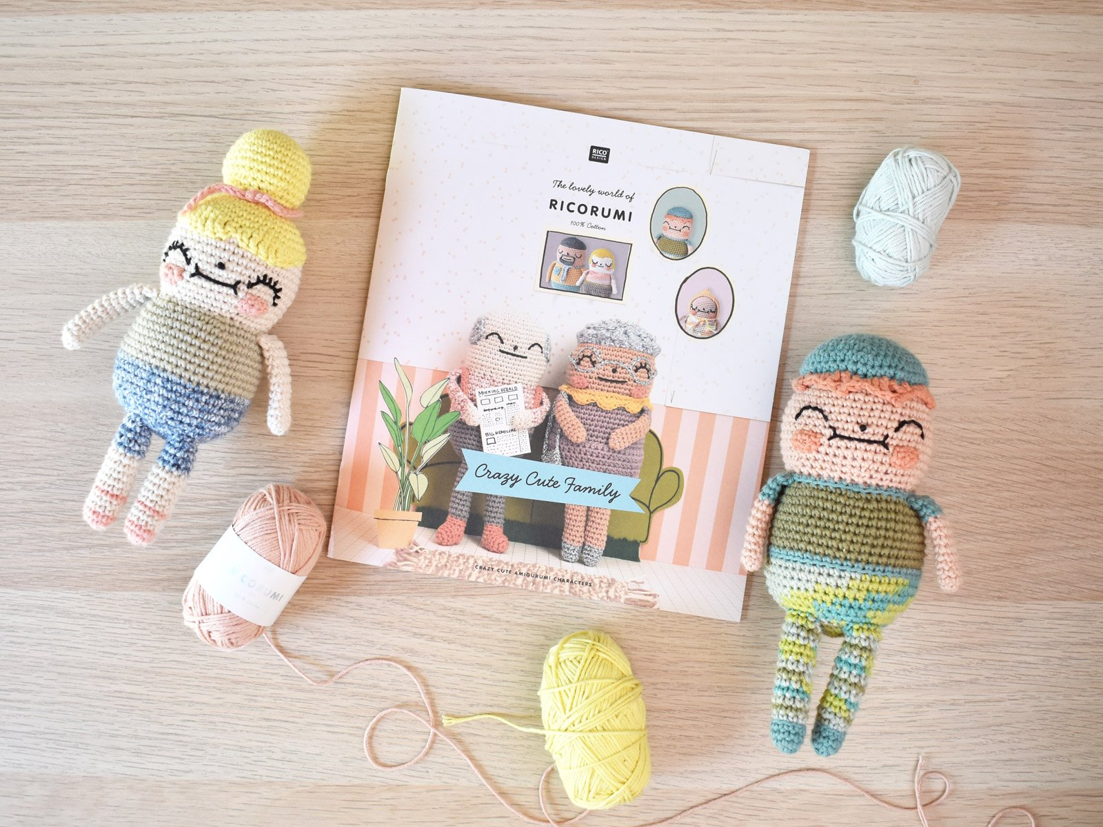 Crazy Cute Family pattern booklet is in the center and a crocheted girl and boy laying on a wooden table with 3 ball of yarn surround them.