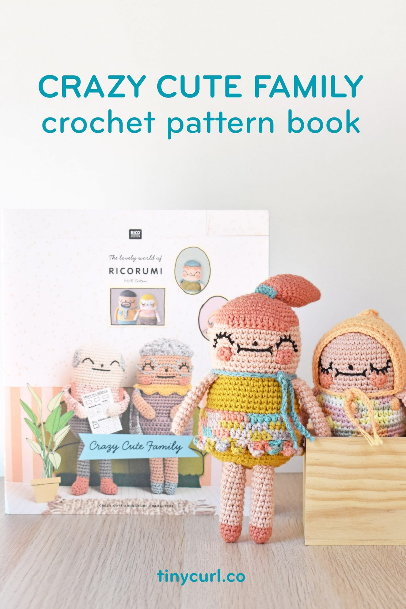 """Crazy Cute Family crochet pattern book"" over photo of a crochet girl and baby. They are propped in front of the pattern book."