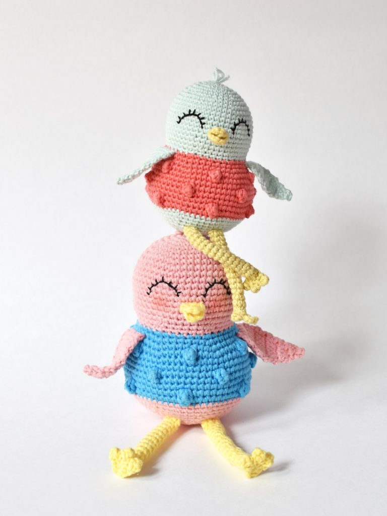 Sweet Bird crochet pattern by Tiny Curl. Two crocheted birds sitting on a white backdrop.