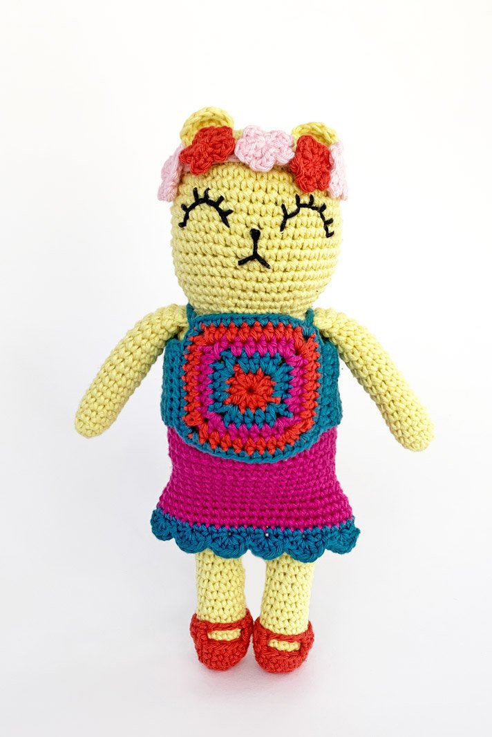 crochet bear in a boho looking halter top, skirt, mary jane shoes, and a flower crown.