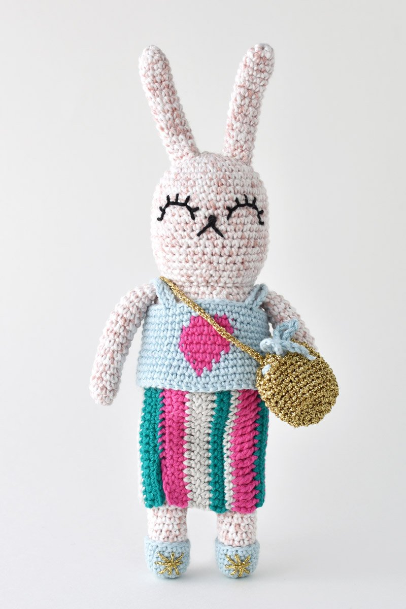 amigurumi bunny in a striped skirt and heart tank top with a gold bucket purse and shoes.