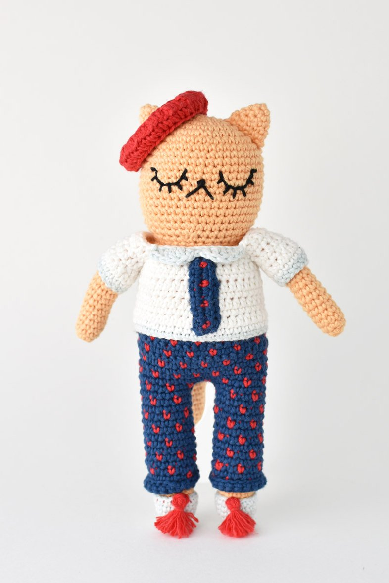 Crochet cat wearing an outfit and beret.