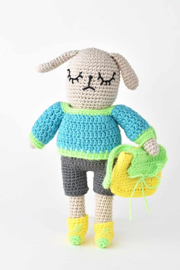 amigurumi dog wearing a crochet sweater, shorts and sneakers and holding a backpack.
