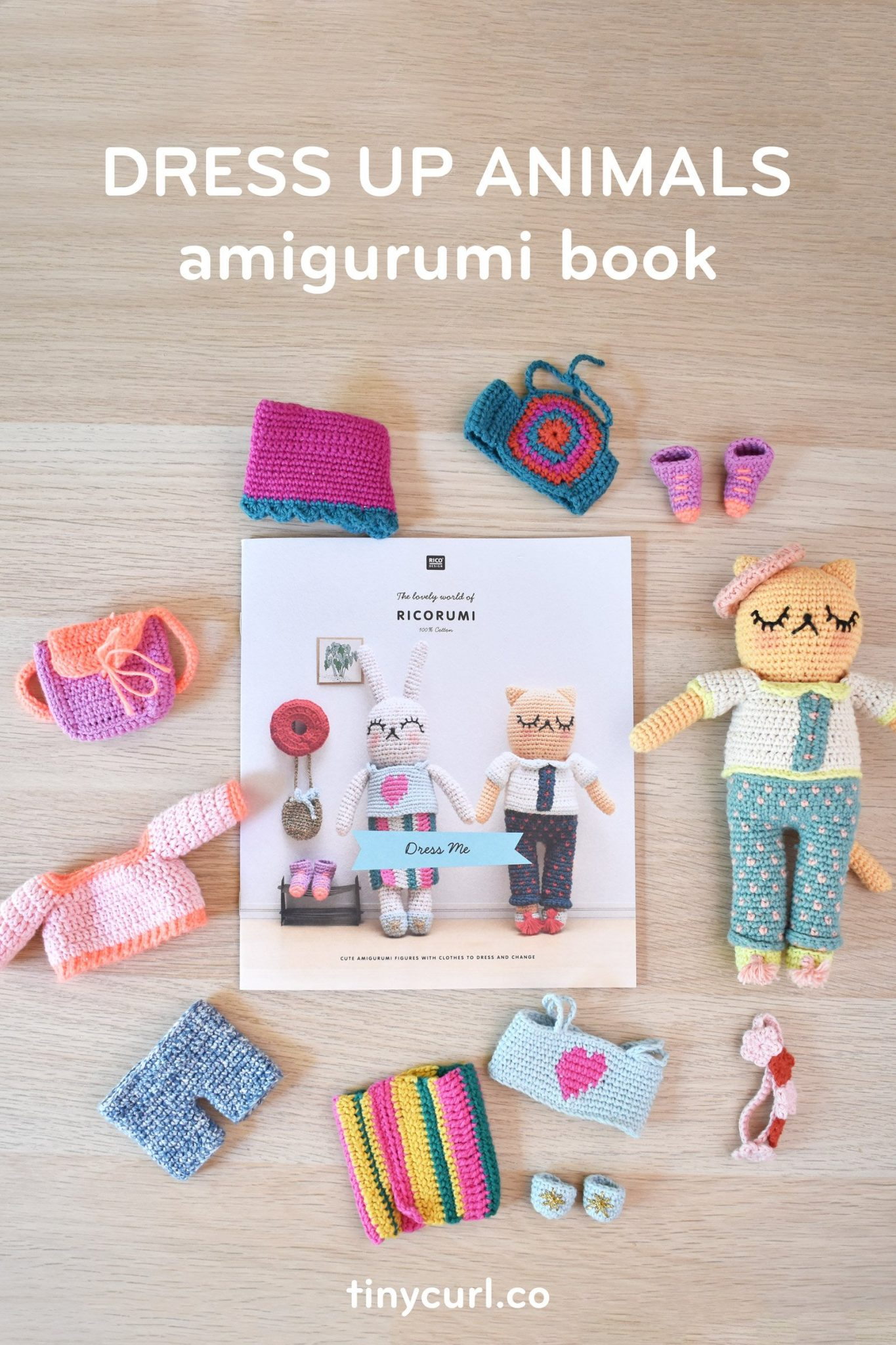 "Ricorumi Dress Me amigurumi book sitting on a wooden backdrop surrounded by the crochet clothes patterns from the book. There is also an amigurumi cat to the right of the book. Text says ""Dress Up Animals amigurumi book"""