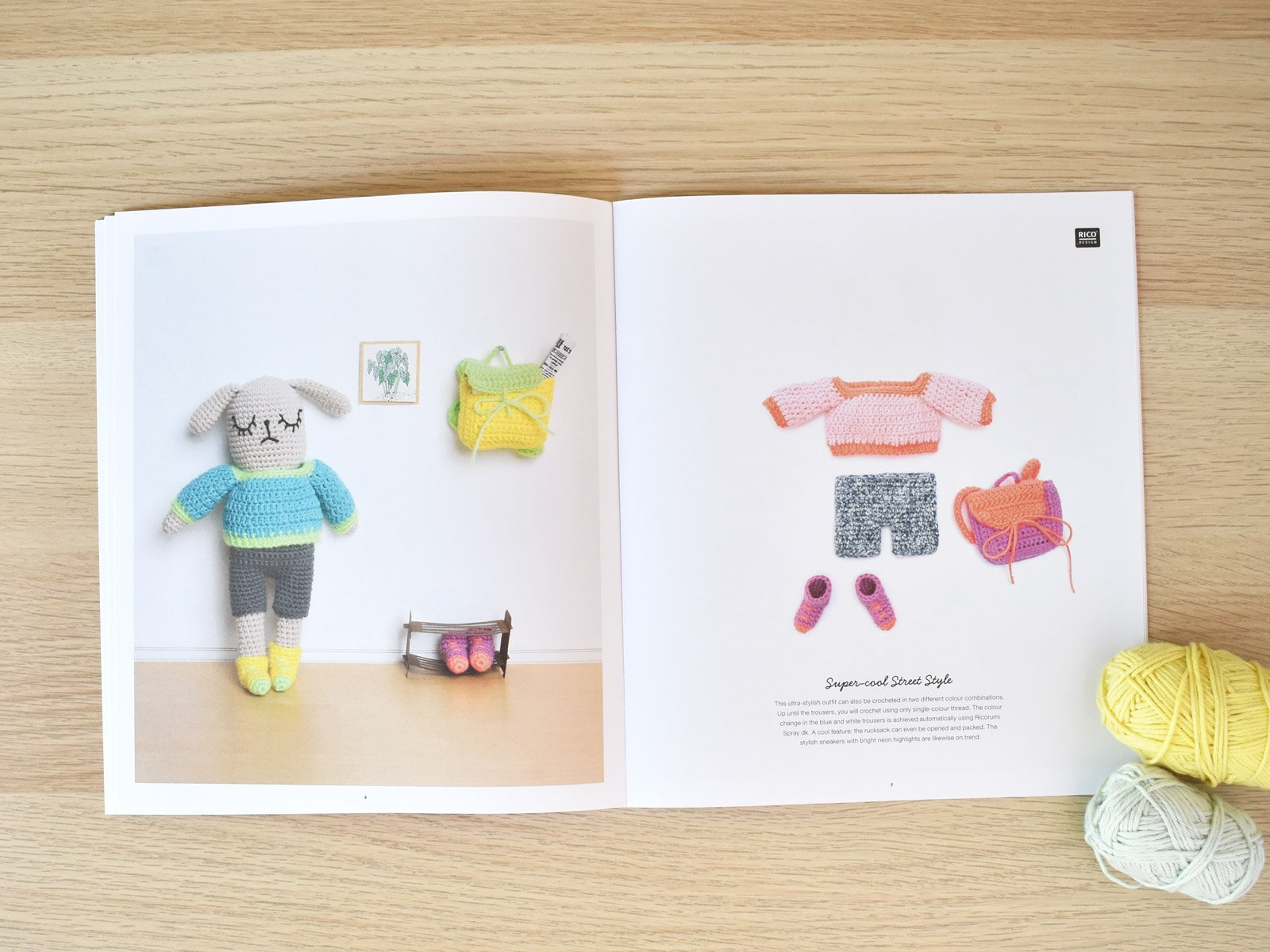 A spread from dress me animal amigurumi book with a couple balls of yarn on a wood backdrop