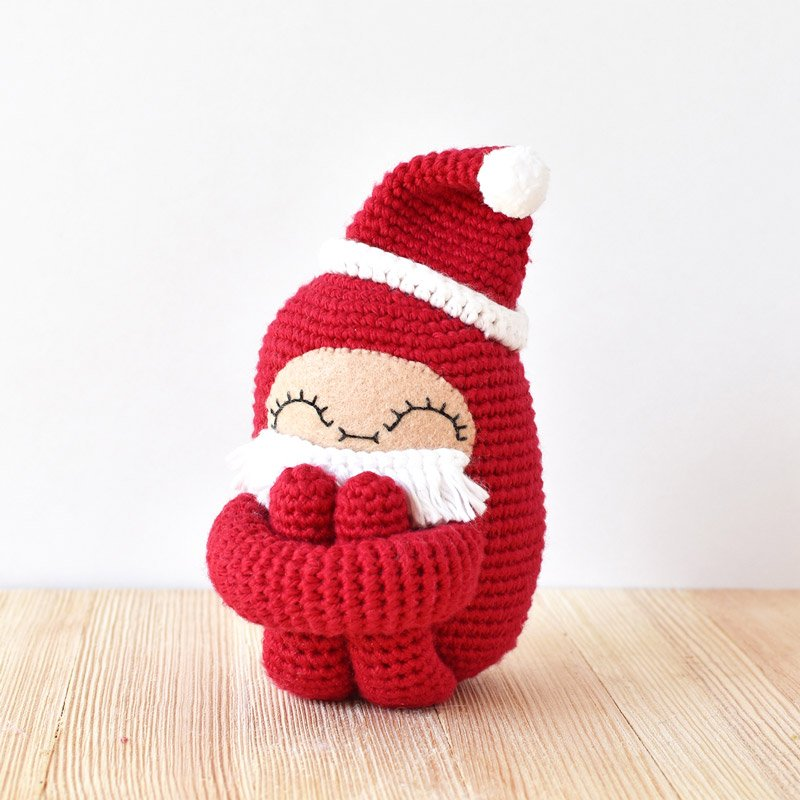 curlie santa crochet doll on a wooden surface