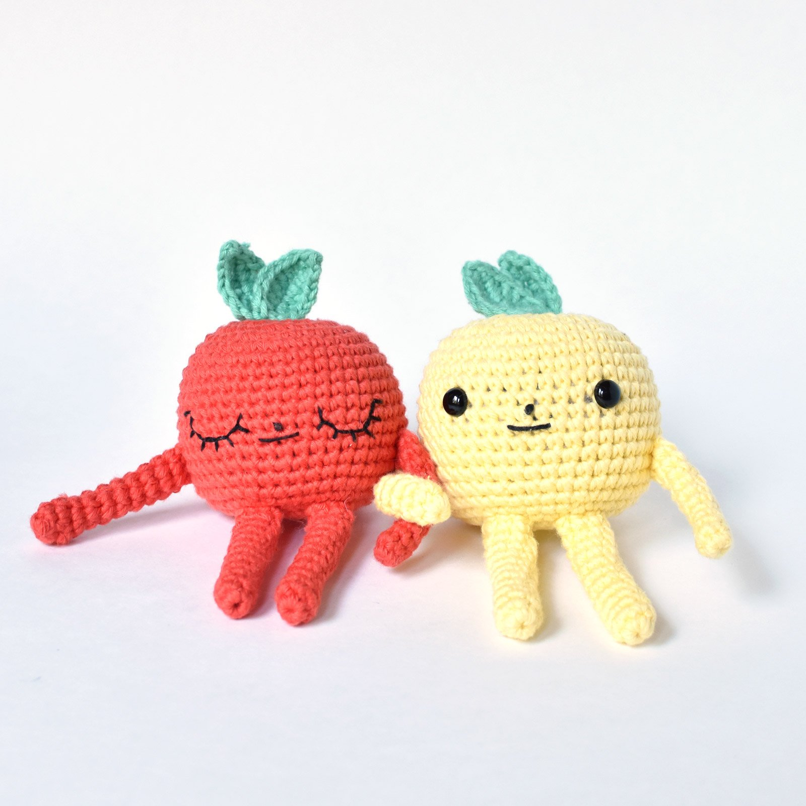 A red and yellow crochet apple with arms linked.