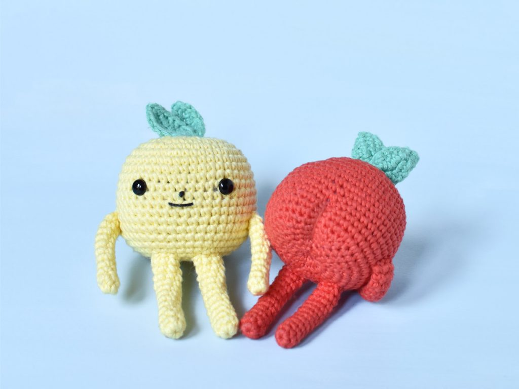 Two crochet apples on a light blue background. One yellow and one red apple. They have arms and legs and you can see the yellow apple's face.