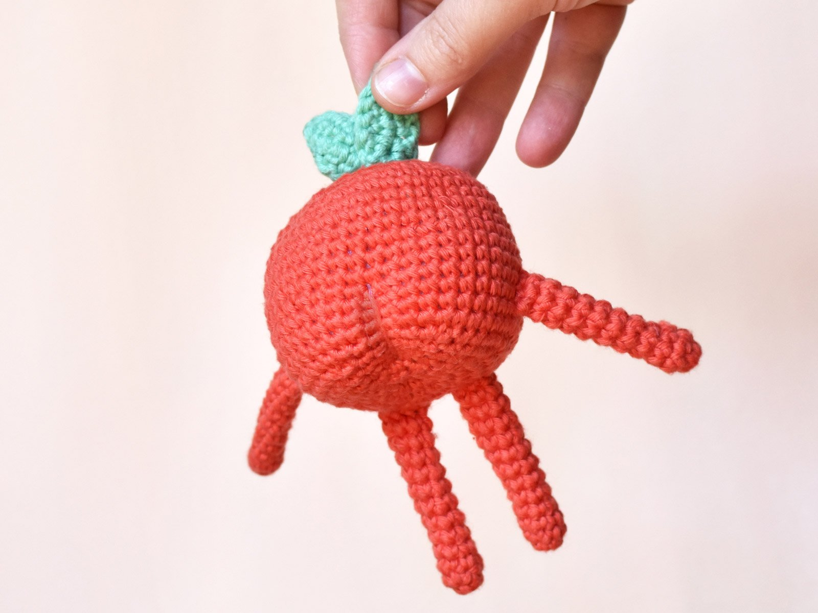 A hand holding onto crochet Apple's leaf, showing the back of the Apple.
