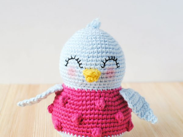 a crochet bird with embroidered eyes