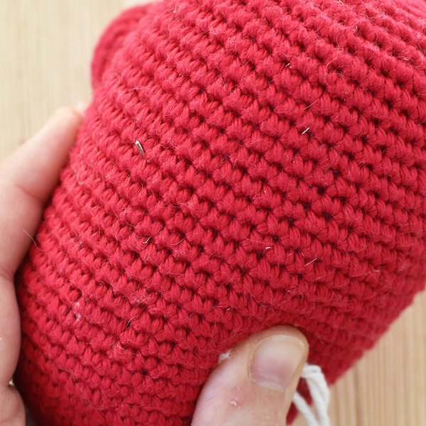 Attaching the crochet Santa beard to an amigurumi doll with needle and yarn