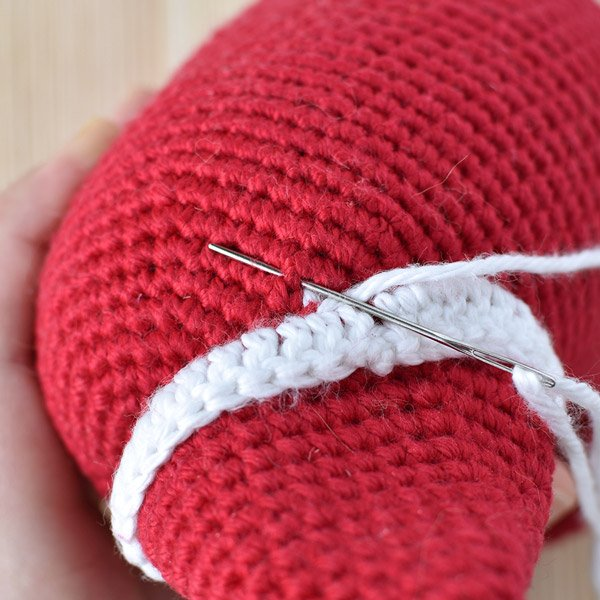 Attaching the crochet Santa hat to an amigurumi doll with needle and yarn.