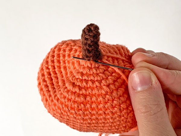 showing how to make lines on side of crochet pumpkin