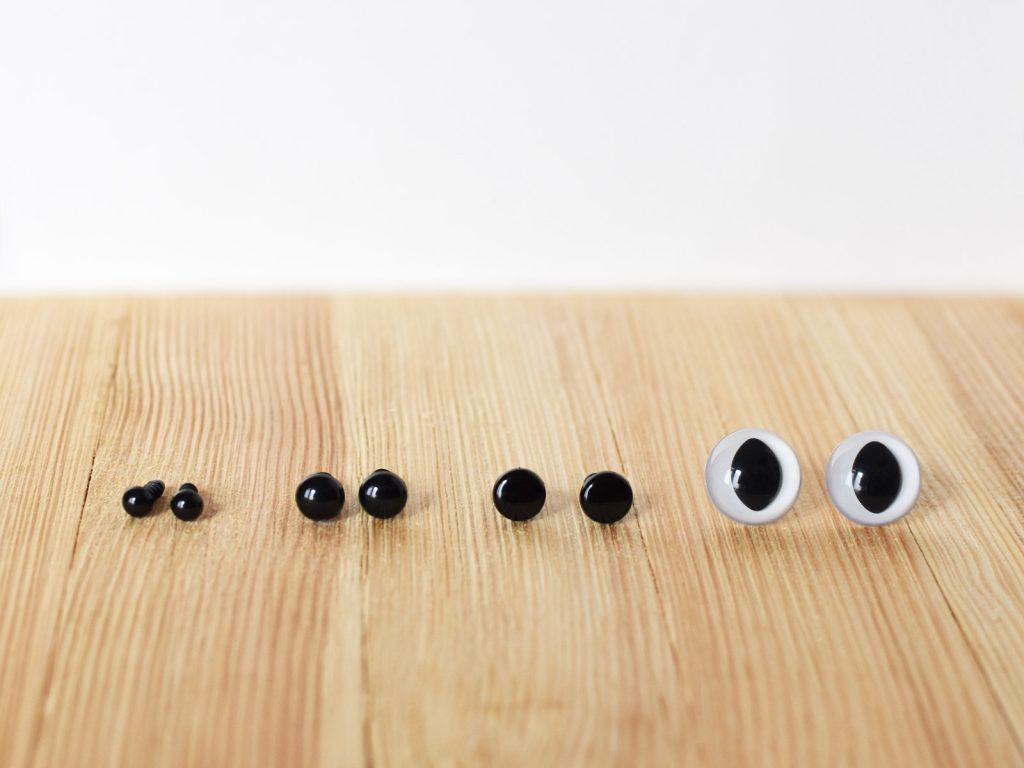 4 pairs of safety eyes on a wooden surface.
